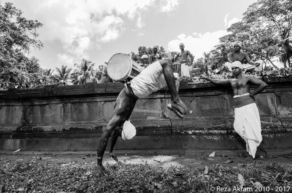 After the banning, Angampora movements and techniques assimilated into other traditional Sri Lankan arts such as dancing and drumming. Pictured is a drummer performing a backflip; a movement influenced by Angampora. © Reza Akram 2010 - 2017